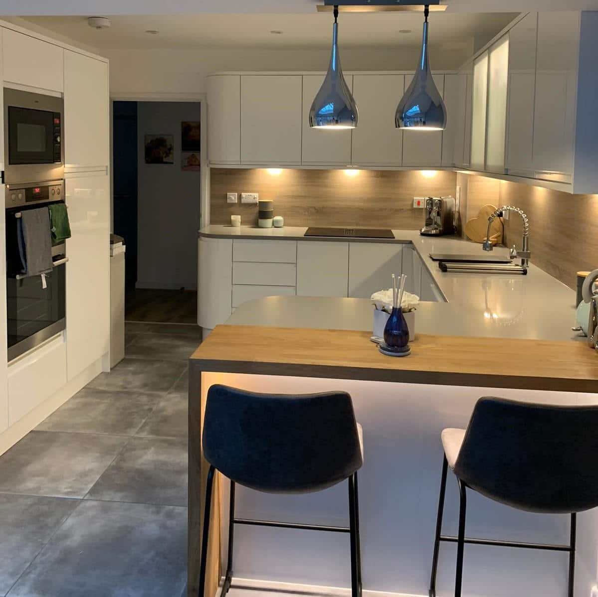Contemporary Strada Gloss White kitchen with peninsula. Laminate splashback